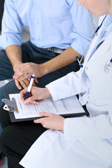 Female doctor holding application form while consulting man patient in hospital. Medicine and healthcare concept
