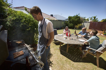 A young guy cooking food for an Aussie barbecue.