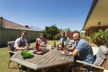 Four people dining in their back yard for an Australian barbecue.