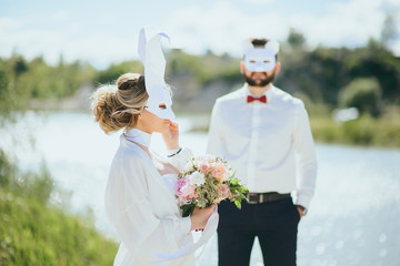 bearded groom and beautiful bride posing in rabbit masks