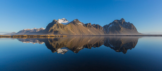 panorama perfectly mirrored vestrahorn mountain, blue sky, morning light