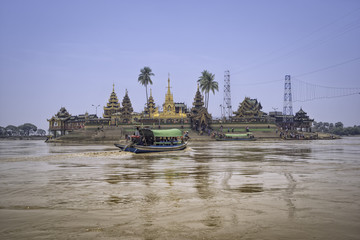 Passengers are transporting tourists across the river to pay homage to the temple.