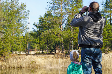 A young ornithologist looking through binoculars in the spring forest to the current birds with his little daughter
