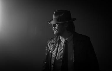 Caucasian Male in vintage trench coat and fedora. Black and white look to light