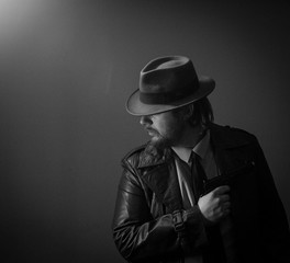 Caucasian Male in vintage trench coat and fedora. Black and white gun hold