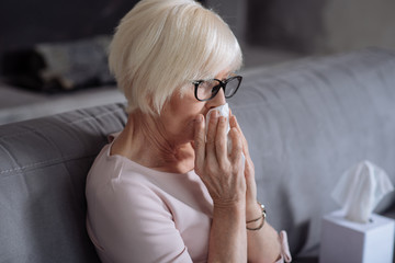 Sick mature women blowing nose and sitting on the settee.