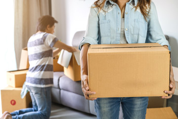 Young happy couple moving in new home and carrying cardboard boxes