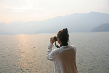 Asian woman taking picture lake landscape  with mountains in the morning