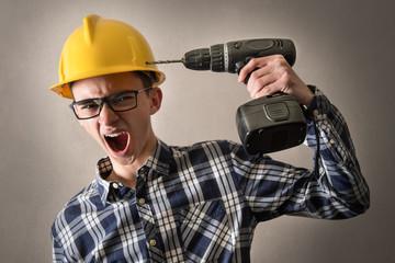 giovane operaio edile simula di spararsi con un trapano