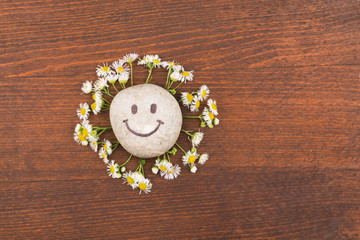 Concept, smiley stone and daisies lying on a wooden surface.