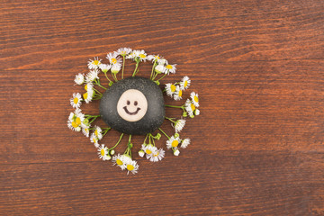 Pyramid smiley stone and daisies lying on a wooden surface.
