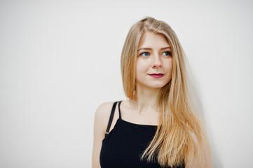 Portrait of blonde girl in black wear against white background.