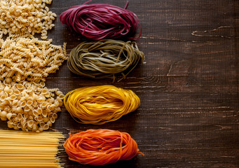 Variety of kinds and forms of dry macaroni. Italian macaroni raw food or texture: pasta, spaghetti, pasta in the form of a spiral.