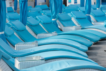 turquoise sun loungers and folded umbrellas in the background of the hotel, the concept of leisure