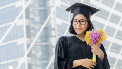 student girl in graduation with flower bouquet