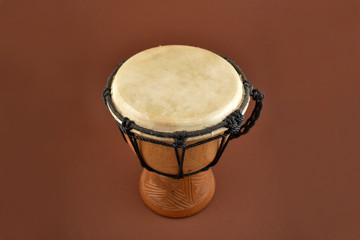African drum stock images. Wooden drum with goat skin, ethnic musical instrument. Djembe Drum on a brown background