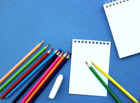 Stationery for students on a blue background. Color pencils, notepad for notes, eraser.