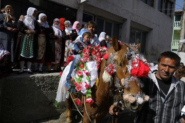 Bulgarian Muslim man and his son ride a horse as they attend a mass circumcision ceremony in the village of Ribnovo