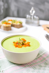 Bowl of Green peas cream soup with baked carrot and microgreen sprouts on the served white wooden table. Healthy food, vegitarian diet concept. Selective focus, space for text.