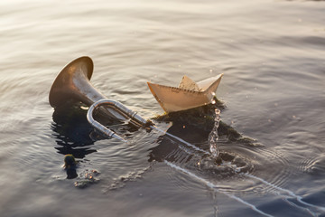 wind instrument pipe lies in the water, in the sea or ocean, next to a paper boat of music, a concept Wall mural