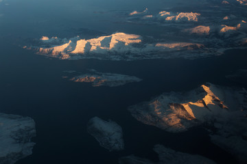 Amazing view of Norway Fjords from plane. Peaks illuminated by sun at sunrise.
