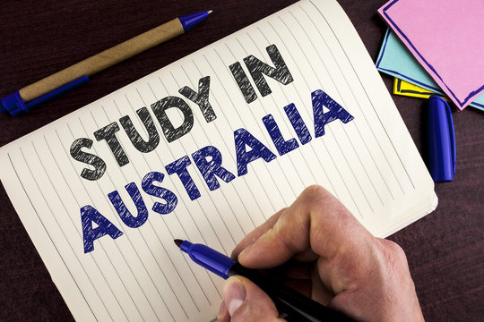 Conceptual hand writing showing Study In Australia. Business photo showcasing Graduate from oversea universities great opportunity written by Man on Notebook Book on wooden background Pen.