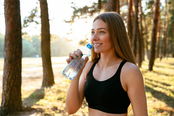 Outdoor photo of young sportive woman drinking a water from bottle after running in the park. Dressed in black tank top.