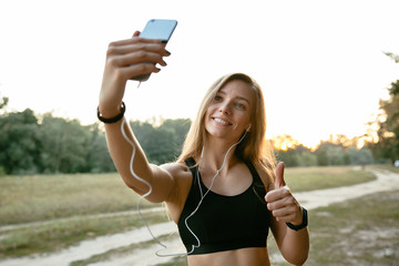 Happy amazing girl in headphones, takes a selfie on mobile phone, showing a thumb up, wearing sport tank top. Outdoors.