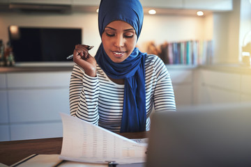Young Arabic entrepreneur reading documents while sitting in her