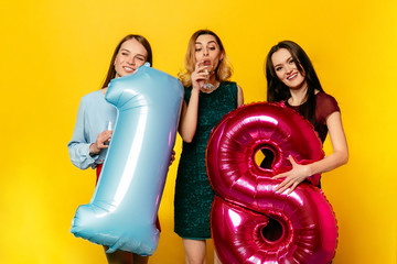 Happy birthday. Three happy pretty women in trendy dressed celebrating an anniversary with champagne, holding balloons. Isolated over yellow background.