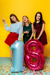 18th Happy birthday anniversary. Cheerful emotions of three young stunning girls having fun while celebrating a holiday with balloons over yellow background.