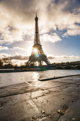 Lens flare through the Eiffel tower during morning on the  Seine river in paris, France