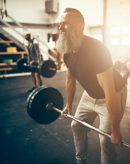 Fit mature man straining to lift weights in a gym