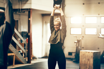Keuken foto achterwand Fitness Smiling young woman swinging a weight at the gym