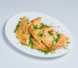 A puff pastry pie with cheese coated with sesame seeds