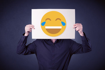 Young businessman hiding behind a laughing emoticon on cardboard