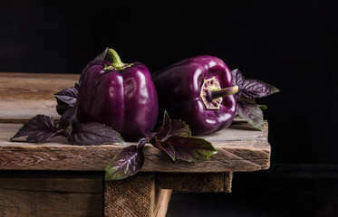 Fresh vegetable. Dark purple peppers with leaves of basil  on old rustic wooden table on black background