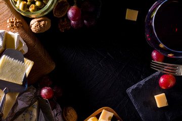 Palette of many types of cheese and some grapes, olives and wine with copy space.
