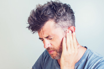 Fototapeta Man with earache is holding his aching ear body pain concept