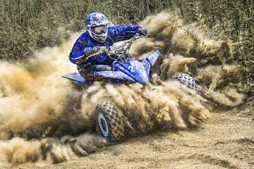 ATV rider creates a large cloud of dust and debris