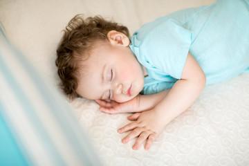 Peaceful baby boy sleeping in a bright room