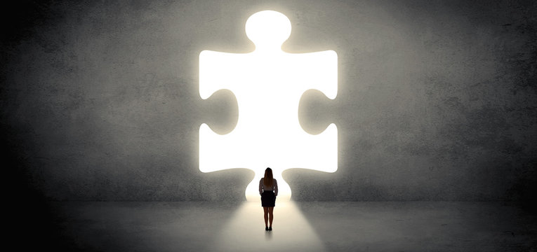 Woman standing and looking to a big puzzle piece
