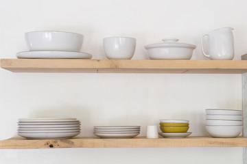 Various ceramic crockery arranged on wooden shelf