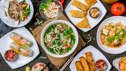 Fototapeta Assorted asian dinner, vietnamese food. Pho ga, pho bo, noodles, spring rolls obraz