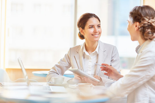 Happy businesswoman listening to explanation of her colleague during presentation of new ideas