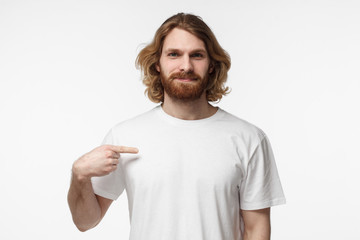 Young bearded man pointing with index finger at blank white tshirt with empty space for your advertising text or image, standing isolated on gray background