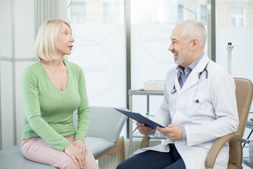 Mature patient in green pullover talking to her therapeutist during appointment in clinics