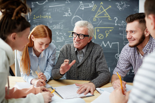 Confident teacher explaining details of his lecture points to group of students after lesson