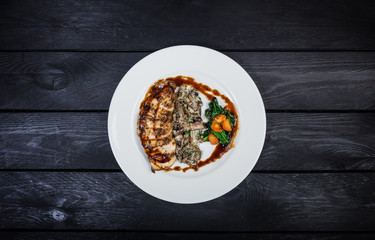 Grilled chicken breast with mushrooms and fried spinach.