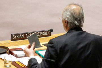 Jaafari, permanent Representative of the Syrian Arab Republic to the United Nations shows the U.N. charter as he speaks during the emergency United Nations Security Council meeting on Syria at the U.N. headquarters in New York